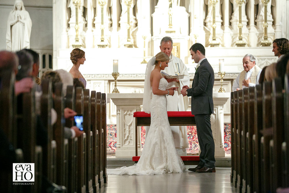 At St James Chapel, bride is putting a ring on her handsome groom's finger.