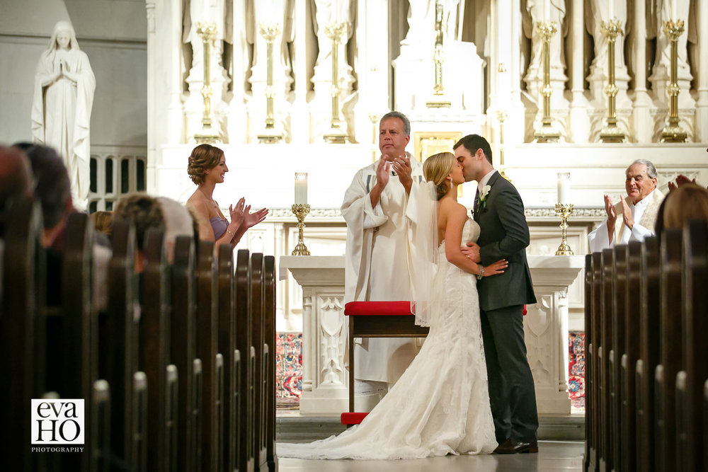 Wedding ceremony at the St James Chapel in downtown Chicago. Bride and groom sealing with a kiss.