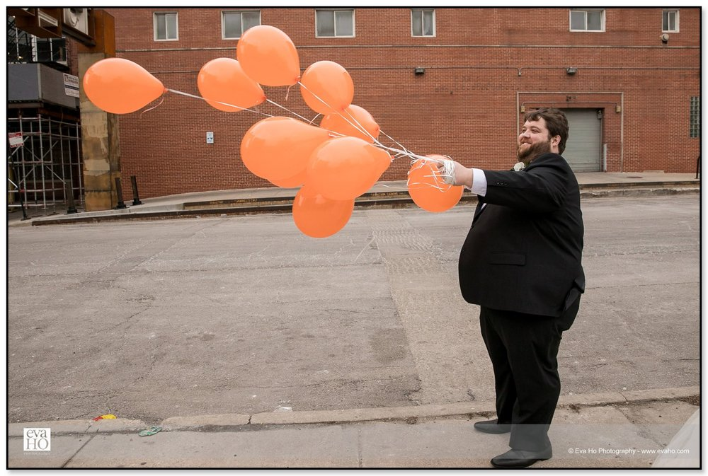 Groom holding orange balloons in Chicago's Fulton Market