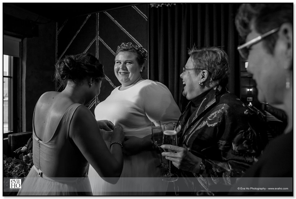 Black & white portrait of bride getting ready in Chicago with family surrounding her