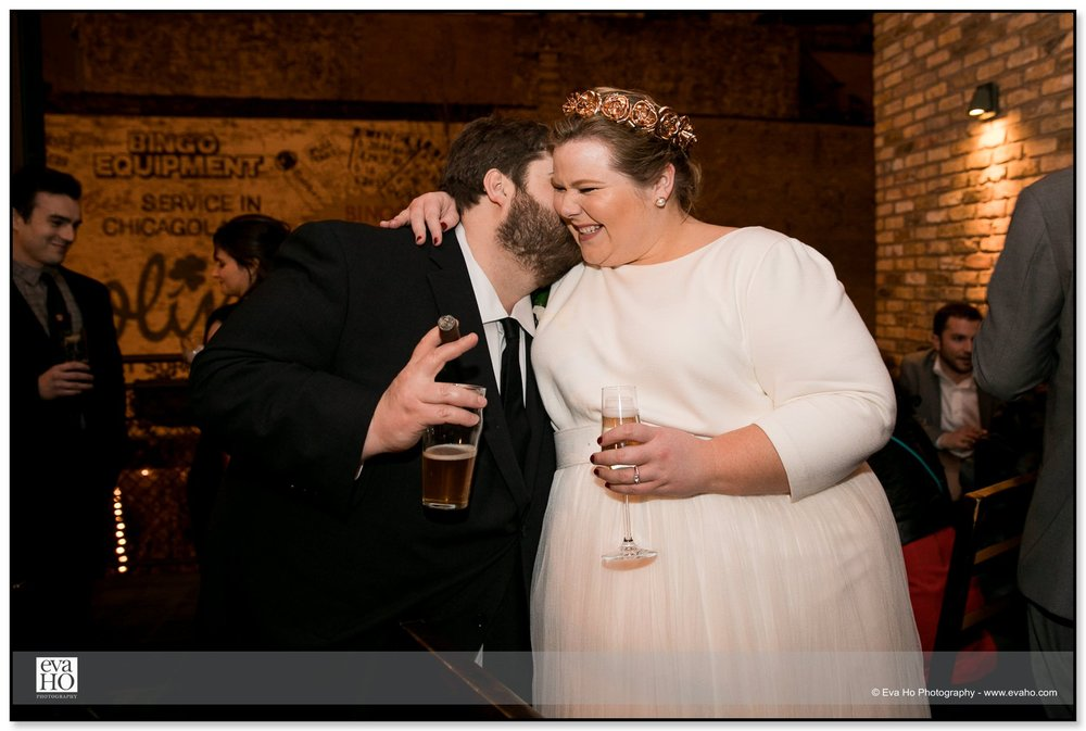 Bride and groom stealing a kiss at a Chicago wedding reception at the Dawson