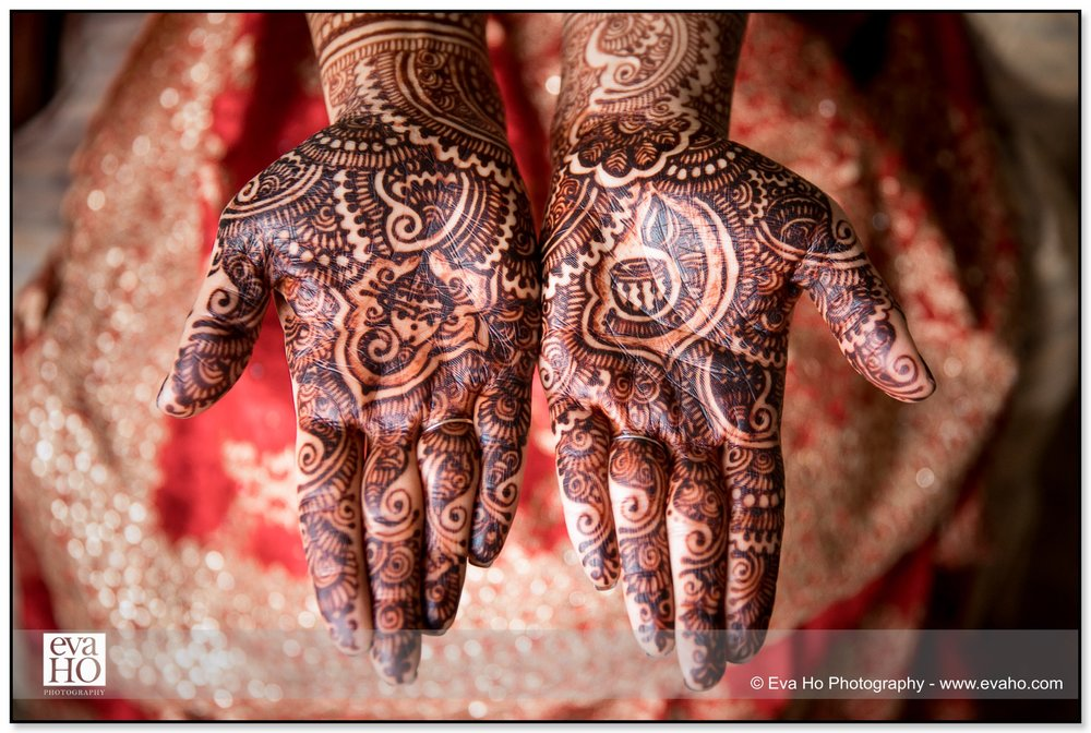 Mehendi designs hand-drawn on the Bride's hands.