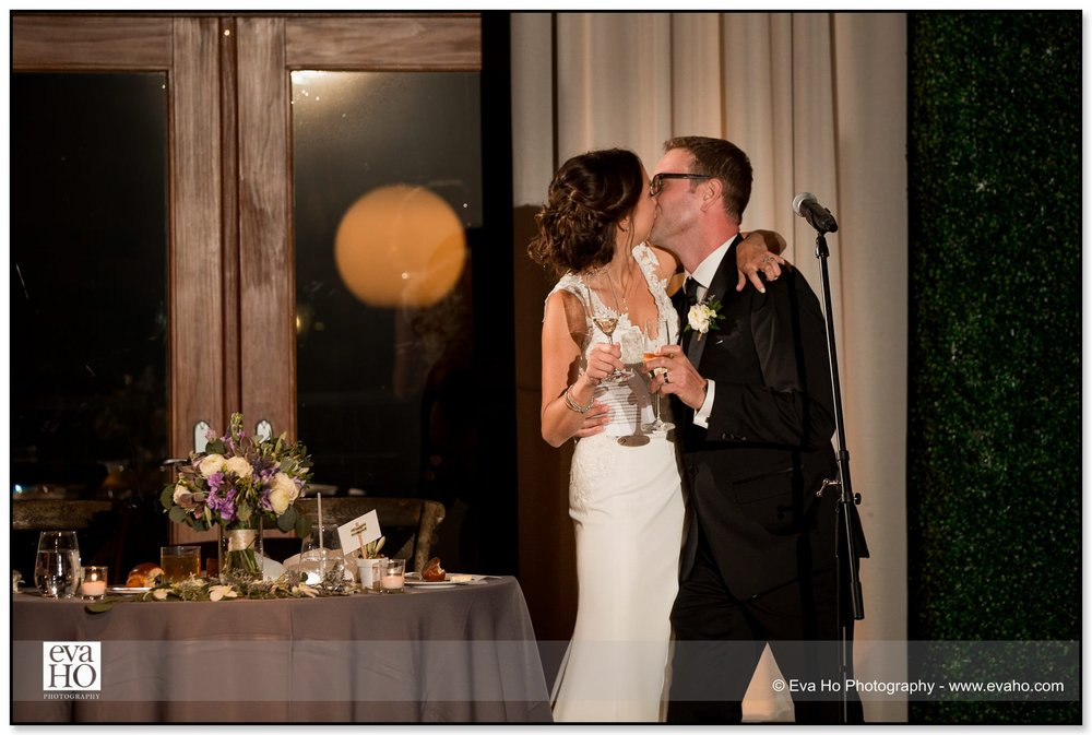 Bride and groom kiss at their wedding reception in the Ivy Room