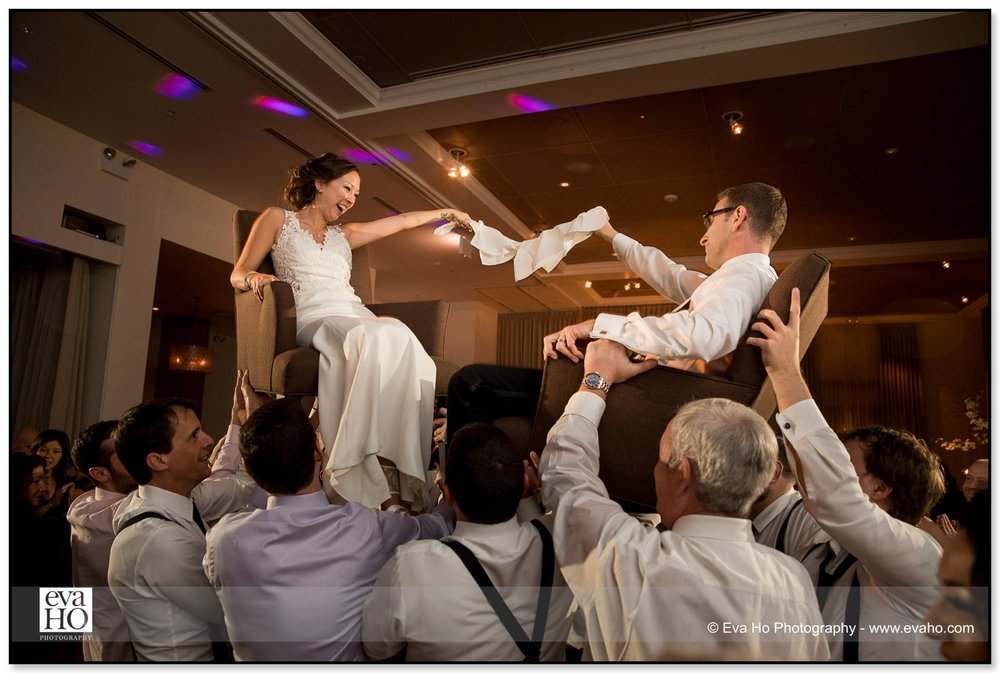 Bride and groom twirl napkins at each other while being lifted into the air during a Jewish wedding reception in Chicago