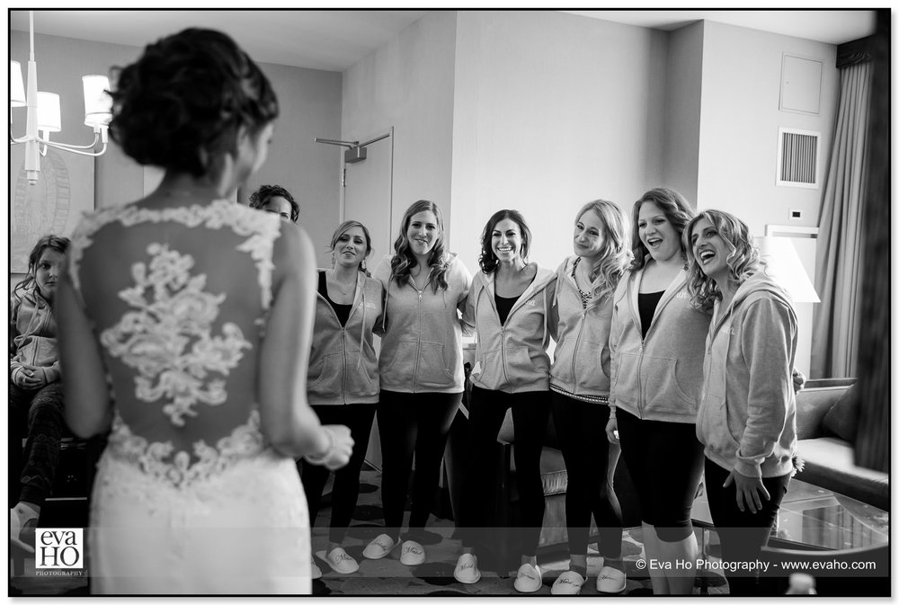 Bride showing off her classically beautiful wedding dress to bridesmaids in Chicago