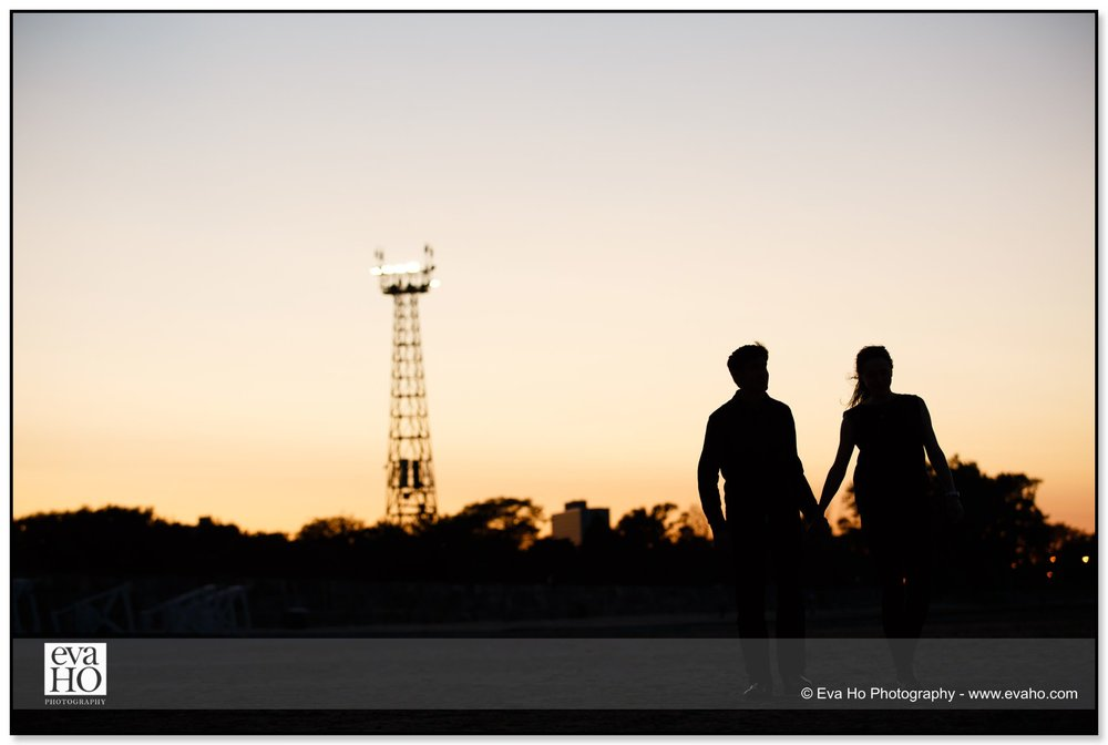 Sunset portrait of a couple walking at Montrose Harbor for their engagement session