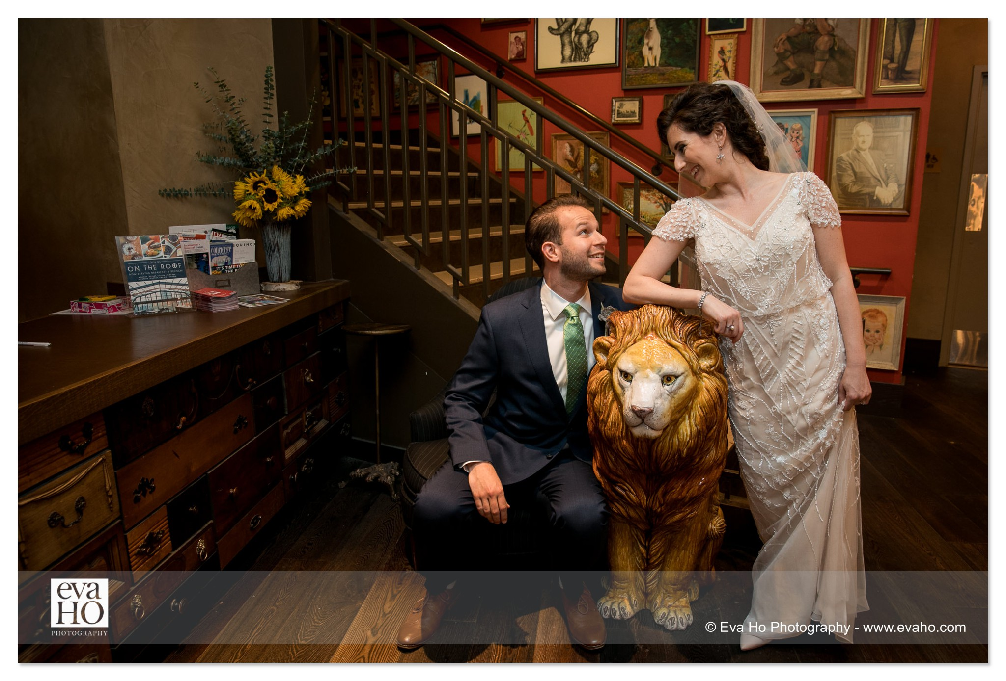 Bride and groom pose with a lion statue
